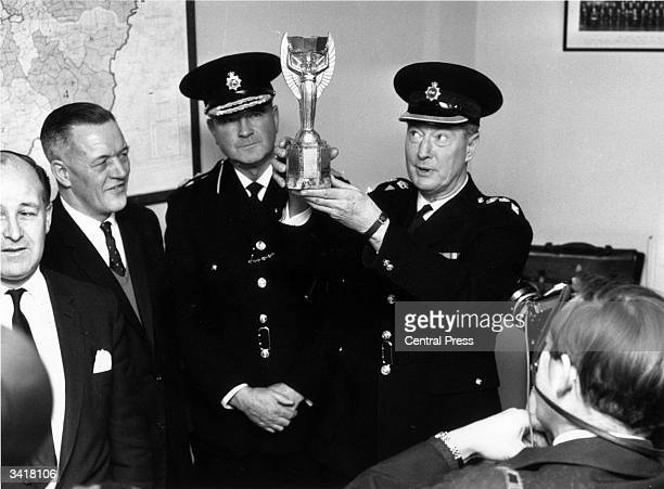 At Cannon Row police station London Chief Superintendent William Gilbert lifts the Jules Rimet trophy for photographers With him are Detective Chief...