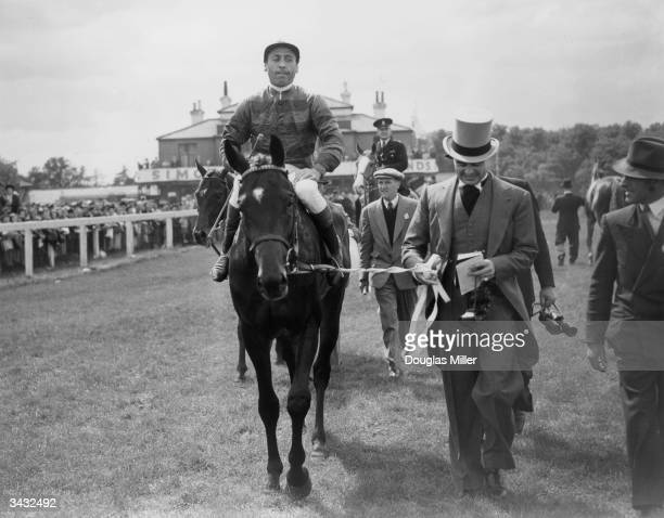 Prince Aly Khan son of the Aga Khan leads in his horse Tulyar Charlie Smirke up after it had won the Derby at Epsom