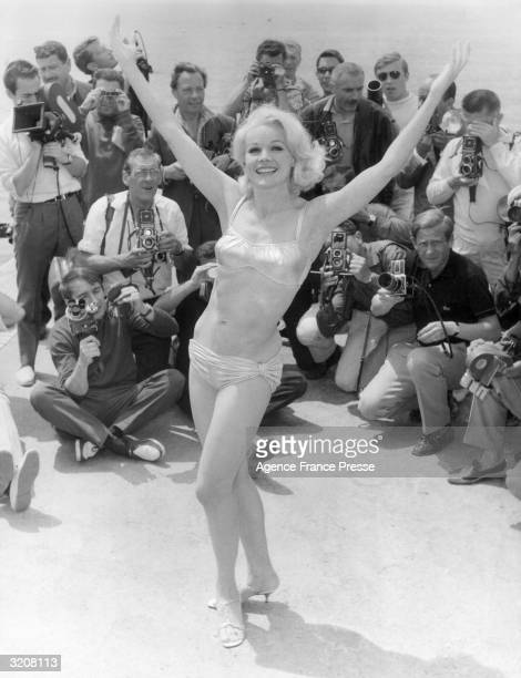 Fulllength image of American actor Carroll Baker posing in a bikini and heels as a crowd of photographers snaps her picture during the Cannes Film...