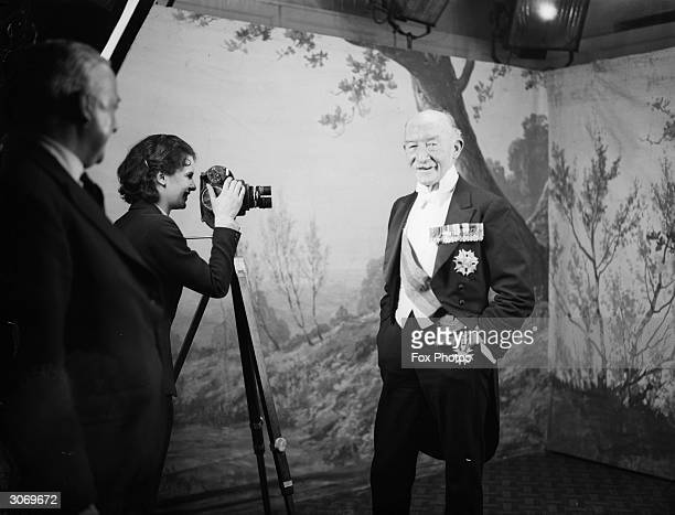 Bemedalled Robert Stephenson Smyth 1st Baron BadenPowell soldier and founder of the Boy Scout movement being filmed by an admirer when he visited the...
