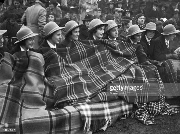 A tartan rug protects a group of English schoolgirls from the cold during a ladies' hockey match between South Africa and England at Merton Abbey...