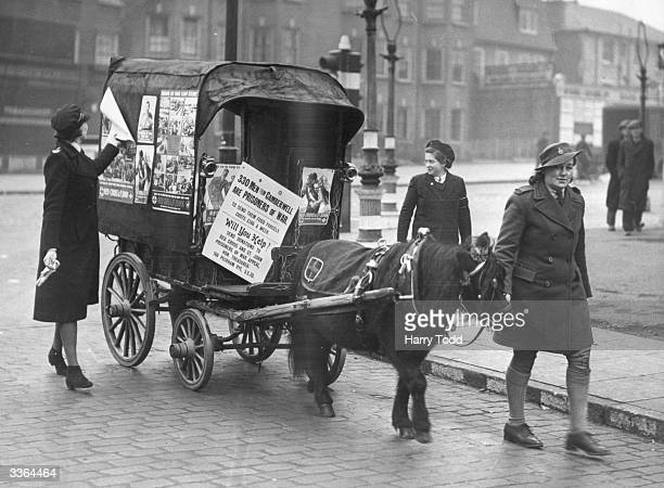 A covered wagon drawn by a Shetland Pony is used to enlist support for the Red Cross Prisoner of War Fund in Camberwell London