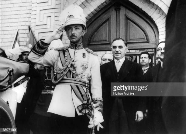 Abdul Illah Regent of Iraq arrives with the Prime Minister on his left receiving the salute of the Guard of Honour The Regent is wearing the Iraqi...