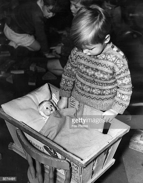 Two year old Nigel Stinton plays with a doll at Egham Day Nursery Surrey