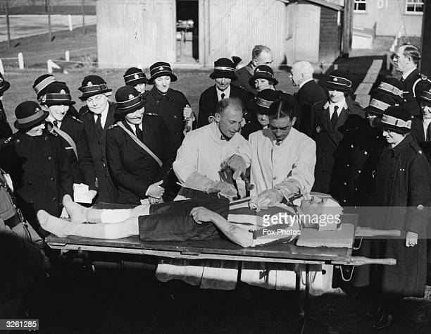 Doctors demonstrating how patients contaminated by mustard gas are washed as soon as they reach hospital to a group of VADs at the AntiGas Wing at...