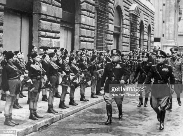 Italian dictator Benito Mussolini inspects Fascist Youth while walking along a street with a group of officers, Italy. The boys wear uniforms and...