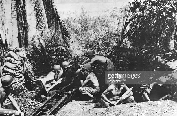 American marines manning a Japanese field gun emplacement which they have captured on Guadalcanal.