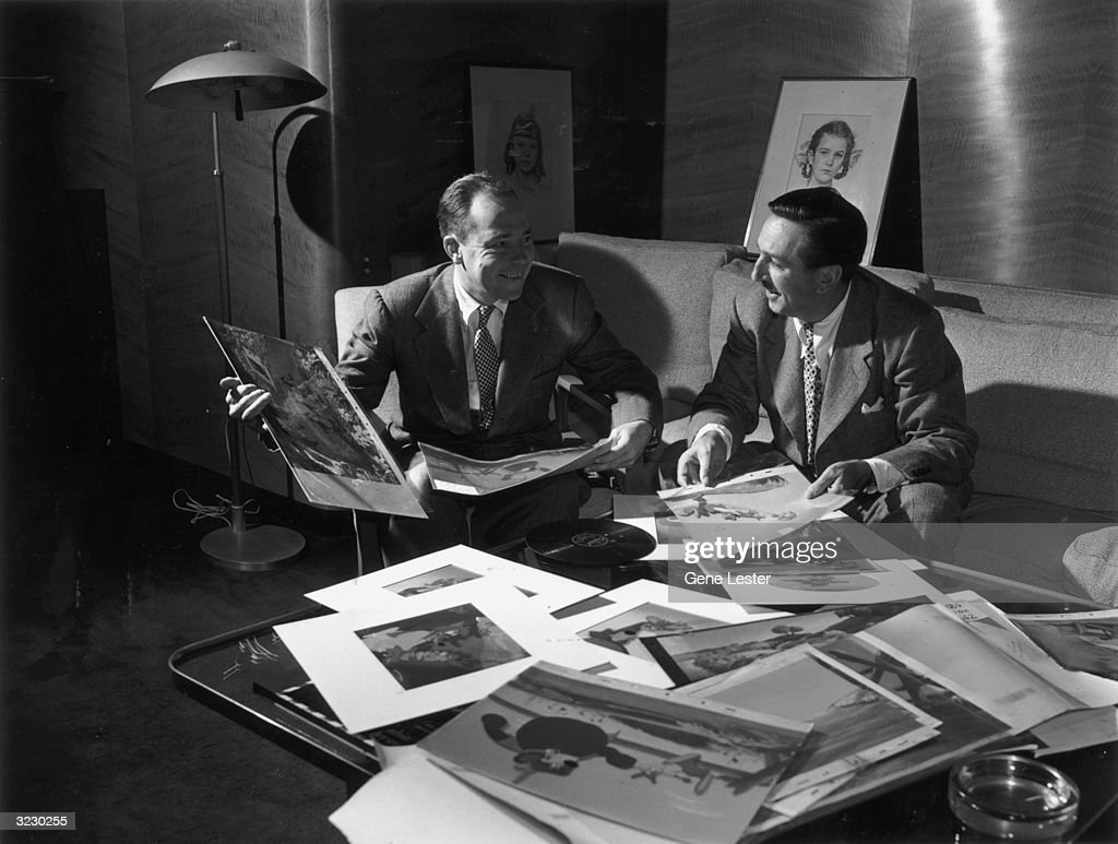 American animator and producer Walt Disney (1901-1966) (right) sits on a couch next to American songwriter Johnny Mercer (1909-1976) in front of cartoon storyboard sketches posted on a cork board for co-directors Harve Foster and Wilfred Jackson's live action/animated Disney film, 'Song of the South'.