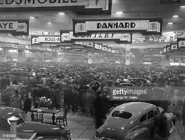 Visitors throng the 34th International Motor Exhibition held at Earls Court London the first Motor Show since the end of World War II