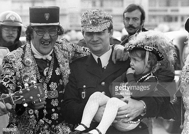 Ricky Conway the Pearly King of Catford and Lewisham London with Brigadier JeanClaude Joly of the French Police holding Conway's twoyearold daughter...