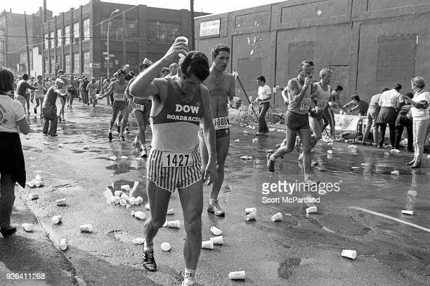 New York A runner is about to pour water over his head as others navigate strewn paper cups littering the streets of Brooklyn during the NYC Marathon