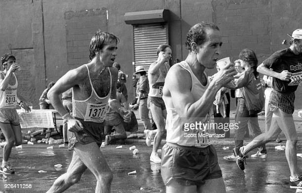 New York Runners drink and pour water over themselves in Williamsburg Brooklyn during the NYC Marathon