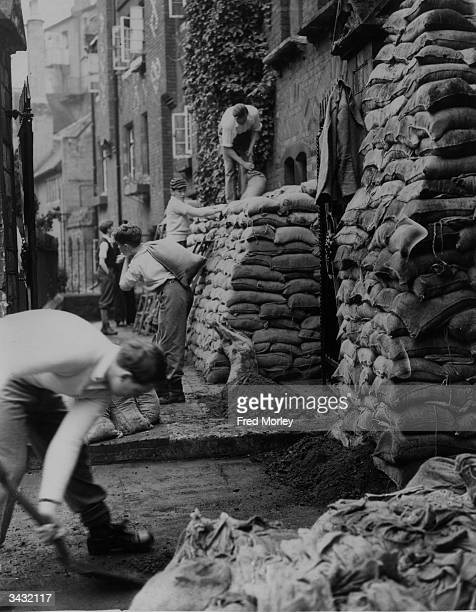 A group of Eton schoolboys piling sandbags around the building for protection against bombing raids