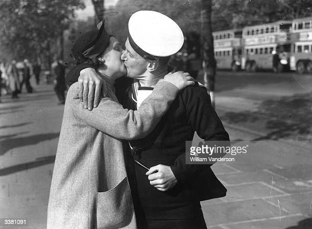 A sailor kisses his sweetheart goodbye in London before reporting for duty at a depot from where a large number of naval ratings will be transported...