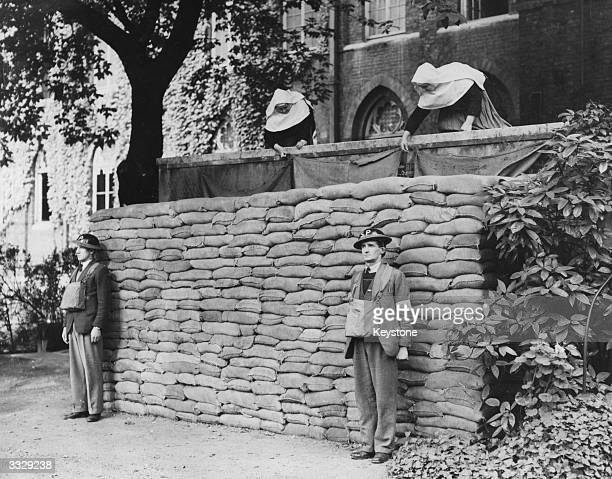 Two ARP sentries stand guard outside The Convent of Assumption Kensington London after its conversion to an ARP Post A sand bag wall shields the...