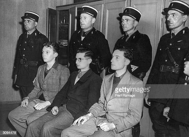 Gendarmes guard three men found guilty of collaborating as agents for the Gestapo From left to right are Yves Maurice Denis sentenced to 15 years...