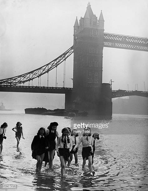 Schoolgirls paddle at Tower Beach by Tower Bridge London