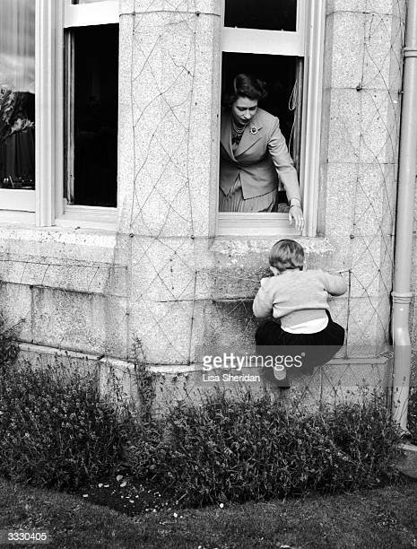 Princess Elizabeth helping Prince Charles to climb through a window at Bamoral Castle Scotland