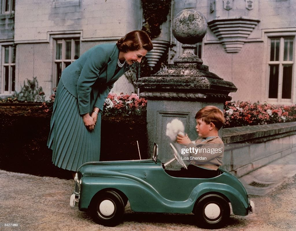 Princess Elizabeth watching her son Prince Charles playing in his toy car while at Balmoral.
