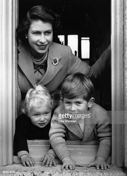 Queen Elizabeth II leaning out of a window with Princess Anne Elizabeth Alice Louise and Prince Charles Philip Arthur George