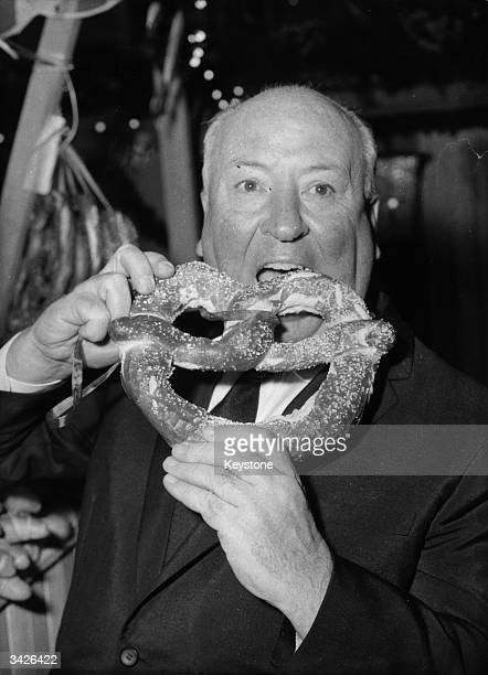 British film director Alfred Joseph Hitchcock eats a pretzel at the premiere of 'Psycho'