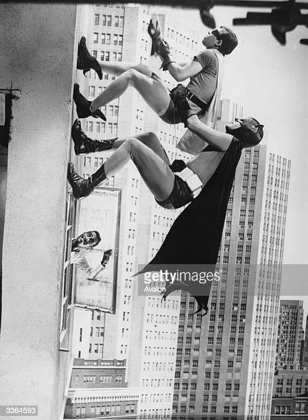 Actors Adam West and Burt Ward as Batman and Robin respectively, 'climbing' on horizontal scenery in a film studio whilst Sammy Davis Junior leans...