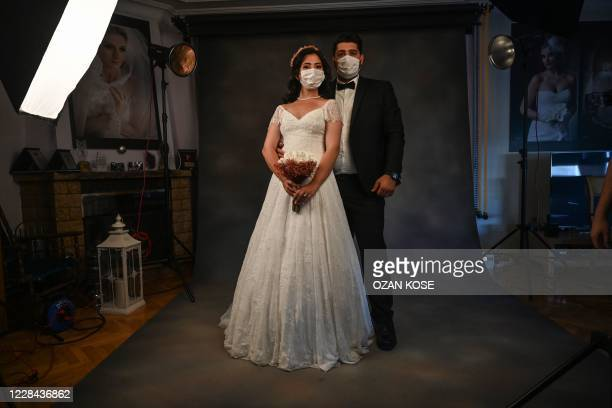 Year-old Ayse Keles and her husband Alp Colak pose with disposable face masks for a wedding photo shoot on September 5, 2020 in Istanbul. - Turkey...