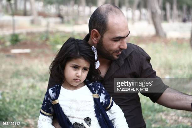 28yearsold Fras Abou AlKheir sits with his daughter in Afrin on May 5 2018 Displaced from their homes in Syria's Eastern Ghouta families sought...
