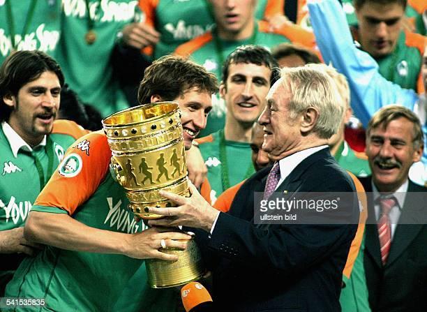 Sportler Fussball DAbwehrspieler Mannschaftskapitän bekommt von Bundespräsident Johannes Rau den DFBPokal überreichtIm Hintergrund die Teamkollegen...