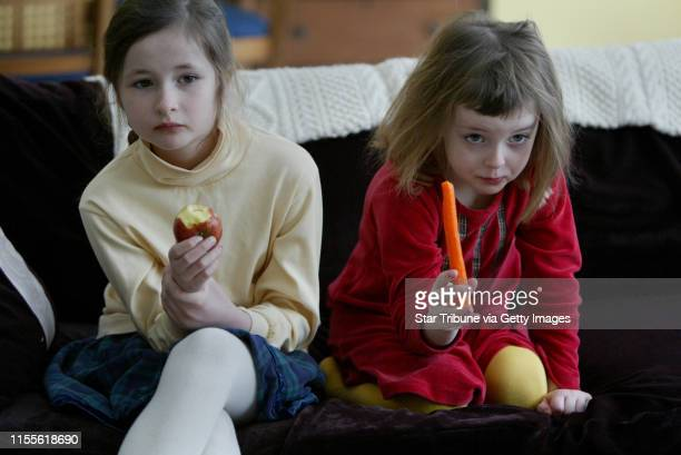 Edina MNleft in yellow 8 yr old Helen Risser and her sister 5 yr old Alloison Risser watch TV on the couch before heading to school both of the girls...
