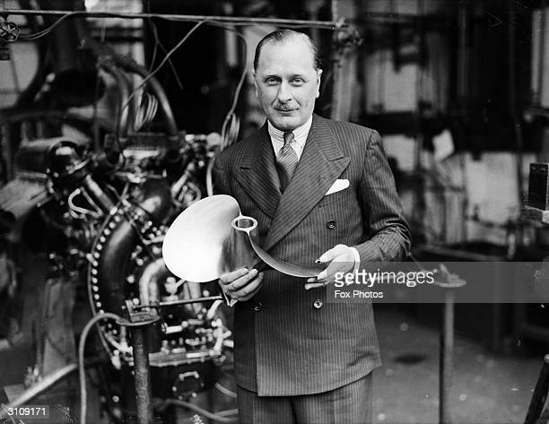 Mr Kaye Don at Rolls Royce works in Derby with a propeller made for Miss England III. It is only 20lbs in weight and has been cut from one piece of...