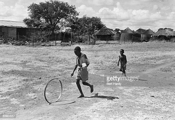 Village in the Serowe area of the Bechuanaland Protectorate, home of Seretse Khama. Two children play with a hoop on dry dusty land in front of their...