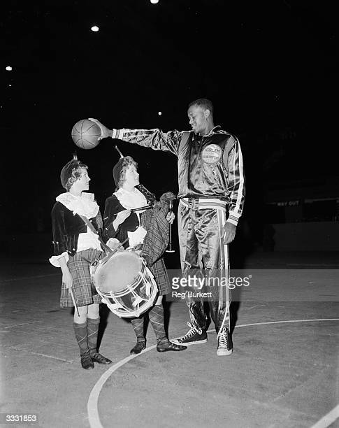 A member of the American Harlem Globetrotters basketball team dwarfs two members of the Dagenham Girl Pipers who stand beneath him with their...