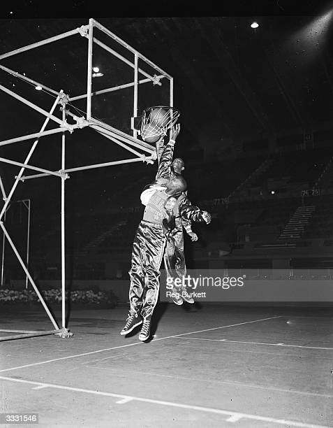Tom 'Tarzan' Spencer and Willie Gardner two members of the American Harlem Globetrotters basketball team net a ball during a warmup