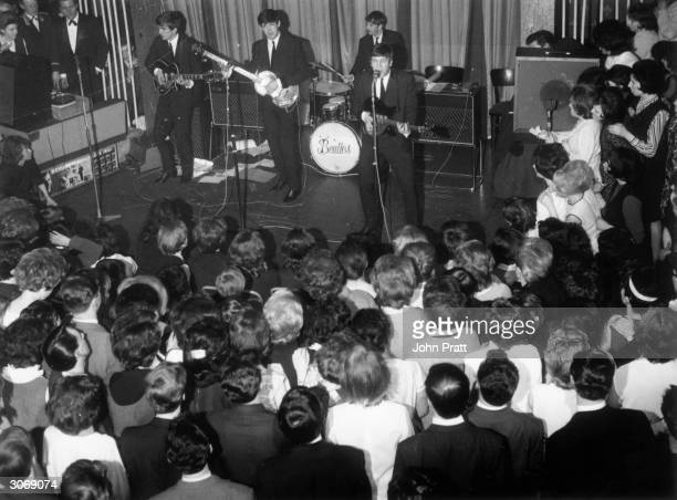 British pop group The Beatles , George Harrison , Paul McCartney, Ringo Starr and John Lennon , playing at the Majestic Theatre, Birkenhead.