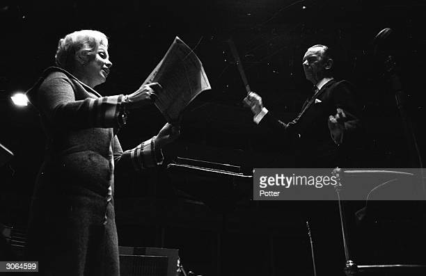 Sir Malcolm Sargent conducts a singer during a rehearsal with the London Symphony Orchestra at the Royal Albert Hall London