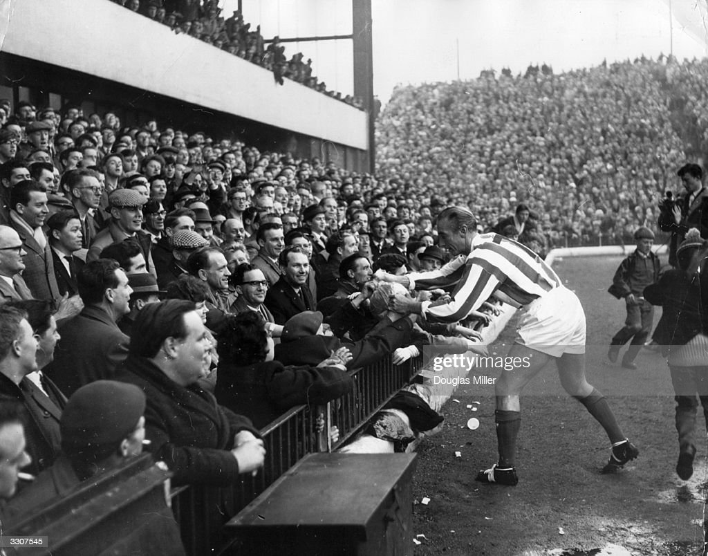 Sir Stanley Matthews, aged 50, presents a souvenir ball to the spectators before playing a farewell match for the Stanley Matthews XI against a World XI at Stoke City's Victoria Ground, where he began his career 33 years earlier.