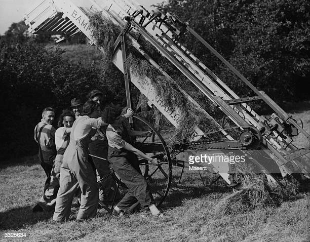 Land girls helping manhandle a hay baler at harvest time