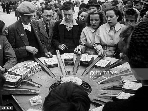 Visitors to Blackpool Pleasure Beach in Lancashire try to win prizes on a sideshow at the fun fair Original Publication Picture Post 1222 Wartime...