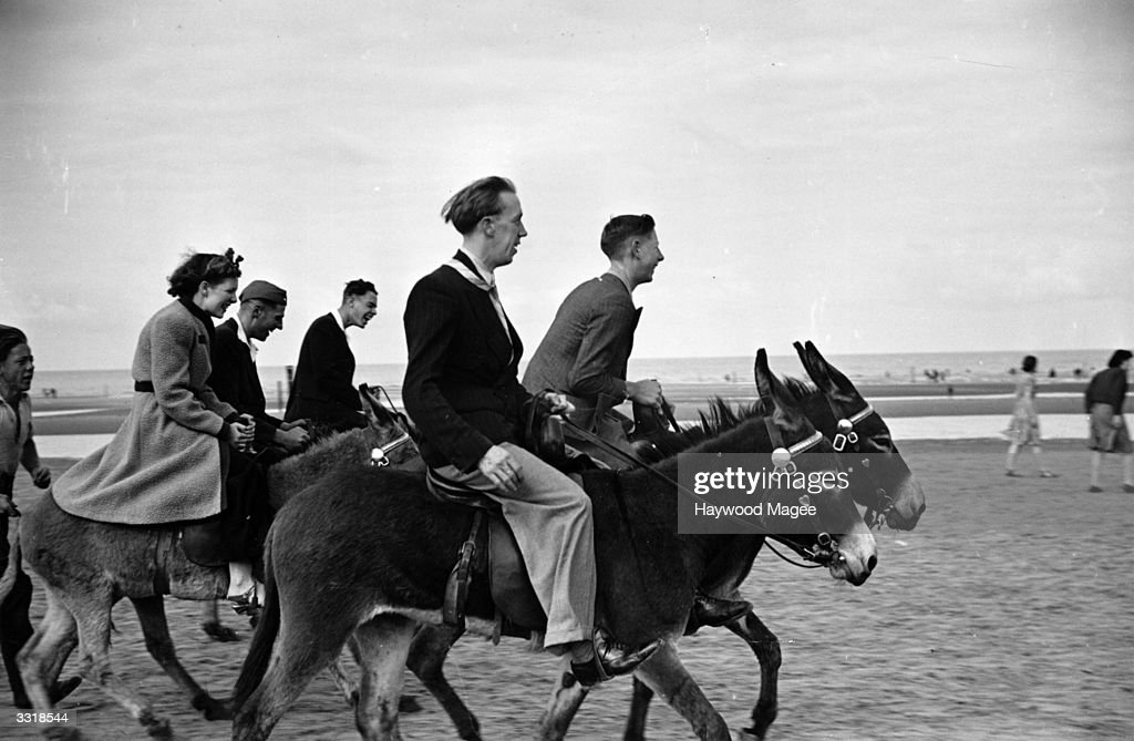 Young people enjoying donkey rides at Blackpool seaside resort in Lancashire. Original Publication: Picture Post - 1222 - Wartime Blackpool - pub.1942