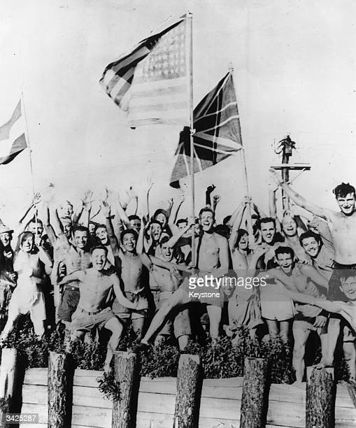 With unrestrained emotion, Allied prisoners of war at Aomori near Yokohama, Japan, cheer wildly as approaching rescuers of the US Navy bring in food,...