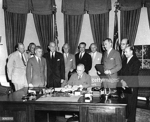 President Harry S Truman signing the North Atlantic Treaty which marked the beginning of NATO behind him are Sir Derrick Hoyes Miller Henrik de...