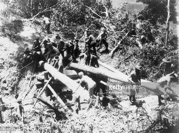 Engineers of General MacArthur's AustralianAmerican task force building a bridge across a stream in the jungles of New Guinea