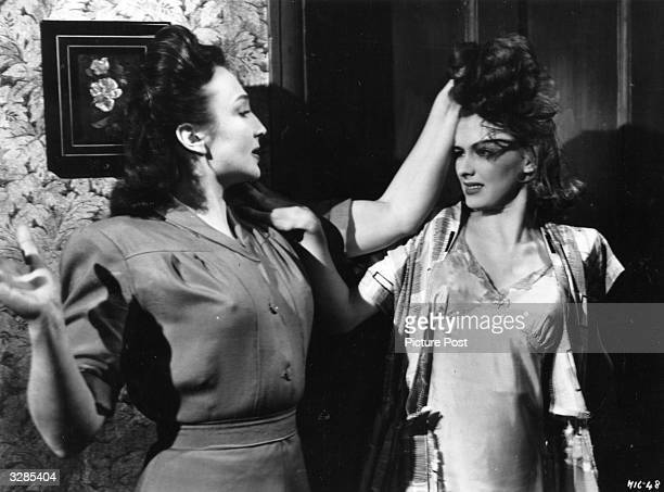 British actress Googie Withers with Susan Shaw in a scene from the film 'It Always Rains On Sunday' directed by Robert Hamer for Ealing Studios...