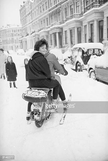 A couple riding on a motorbike in Earls Court London with the help of a set of skis