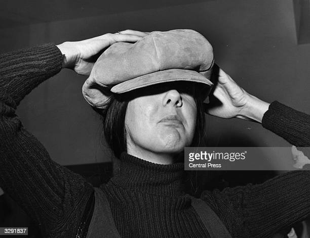Schoolteacher Margaret Craig trying out the fashionable new Jackie Coogan style suede cap at Selfridges department store in London's Oxford Street