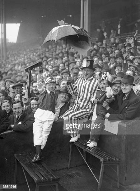 Football supporters, one dressed in a striped suit holding up an umbrella, another with a football rattle, at Highbury, London, for a FA Cup tie...