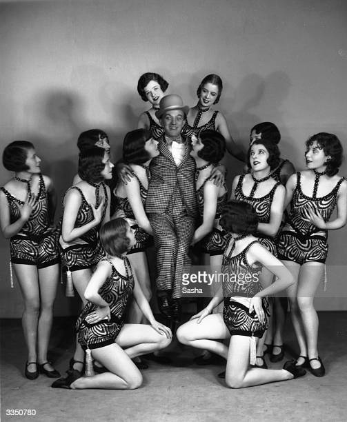 Cast members of the show Burlesque A checksuited comedian is given a lift by members of the chorus