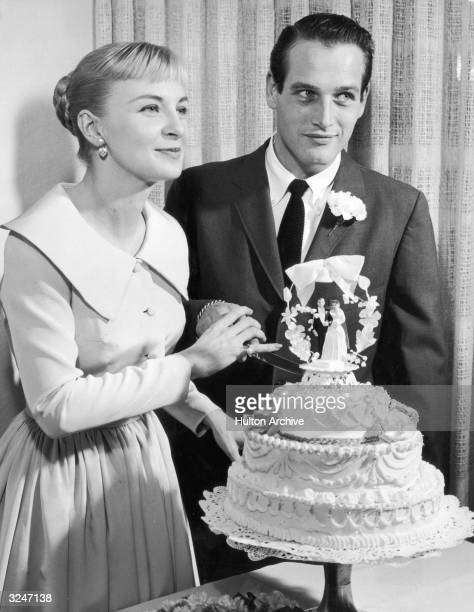 American actors Joanne Woodward, wearing a pale-colored dress with a pleated skirt, and Paul Newman, wearing a suit and tie, holding a knife together...