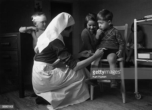A children's nurse at a clinic at East Finchley north London tying a bandage on a little boy's leg Original Publication Picture Post 1760 Nursery...